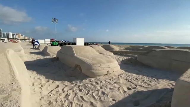Artista recria engarrafamento de trânsito em tamanho real em areia