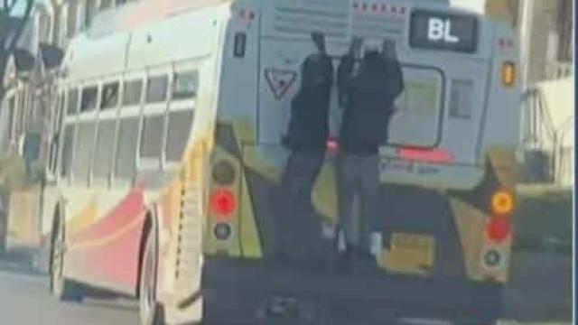 Homens apanhados em vídeo pendurados à boleia na traseira de um autocarro