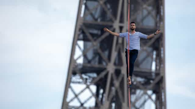 Acrobata atrai multidão em travessia de slackline desde a Torre Eiffel