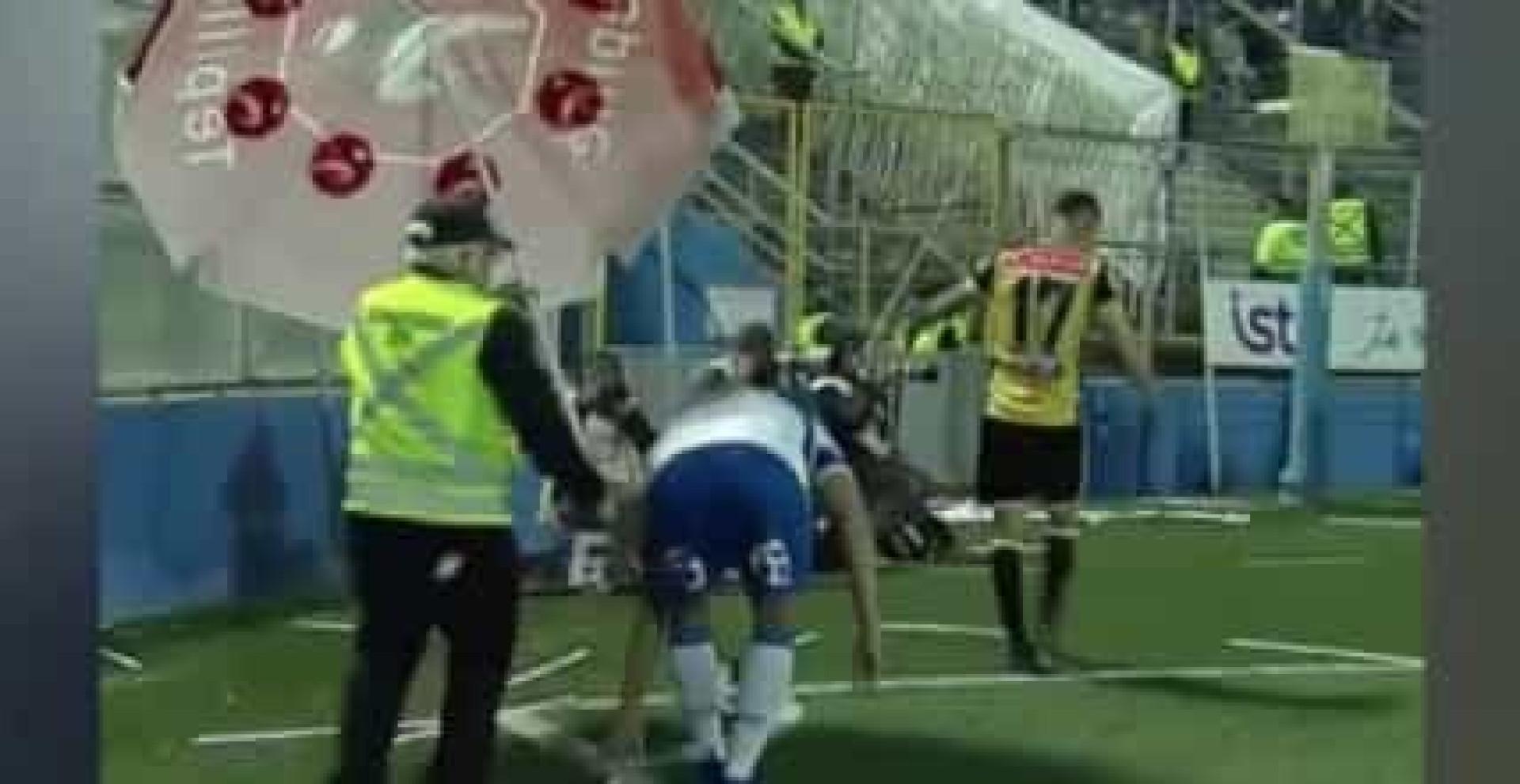 Jogador a ser atacado das bancadas e steward protege-o com.. guarda-sol