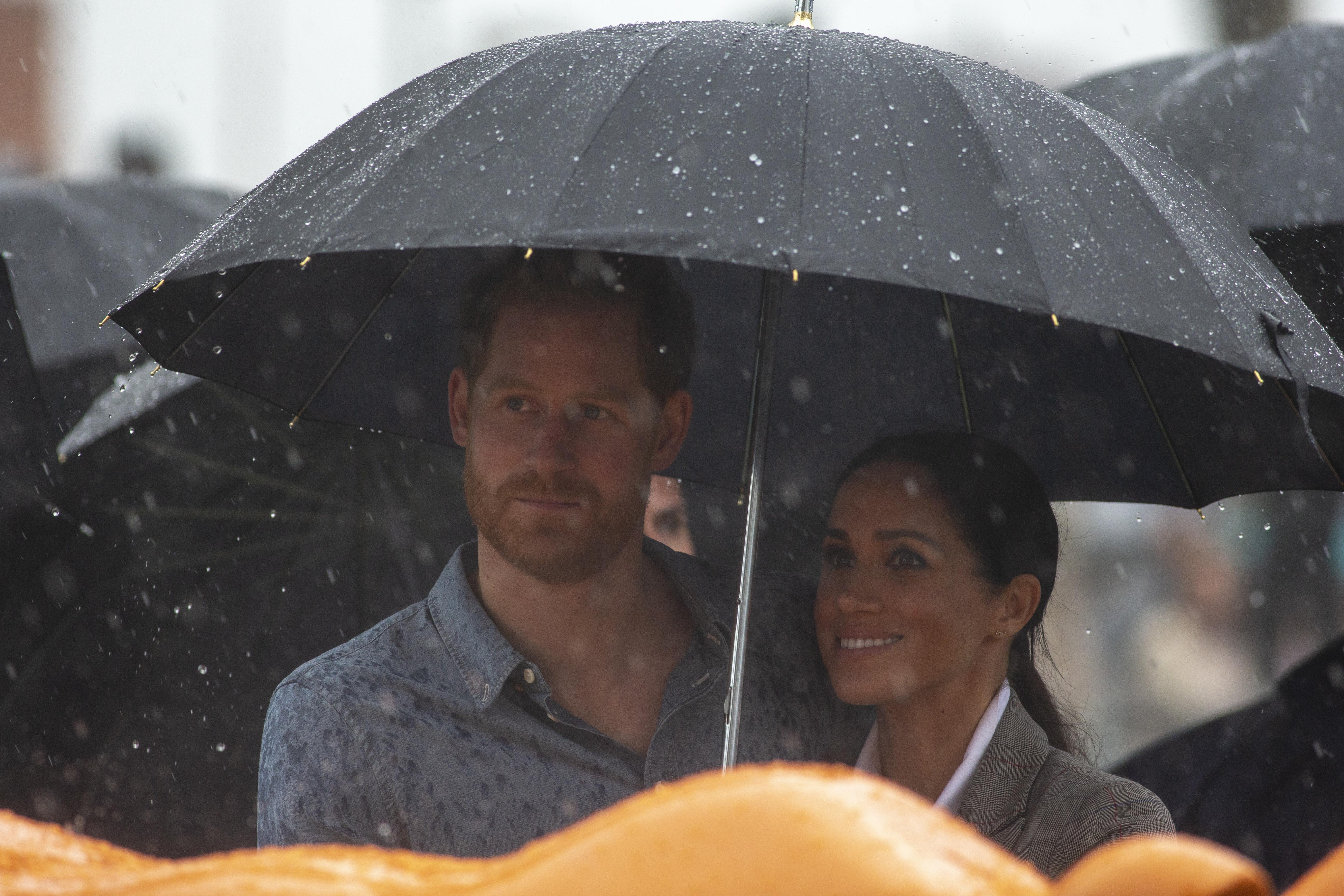 O momento adorável em que Meghan Markle tenta proteger Harry da chuva