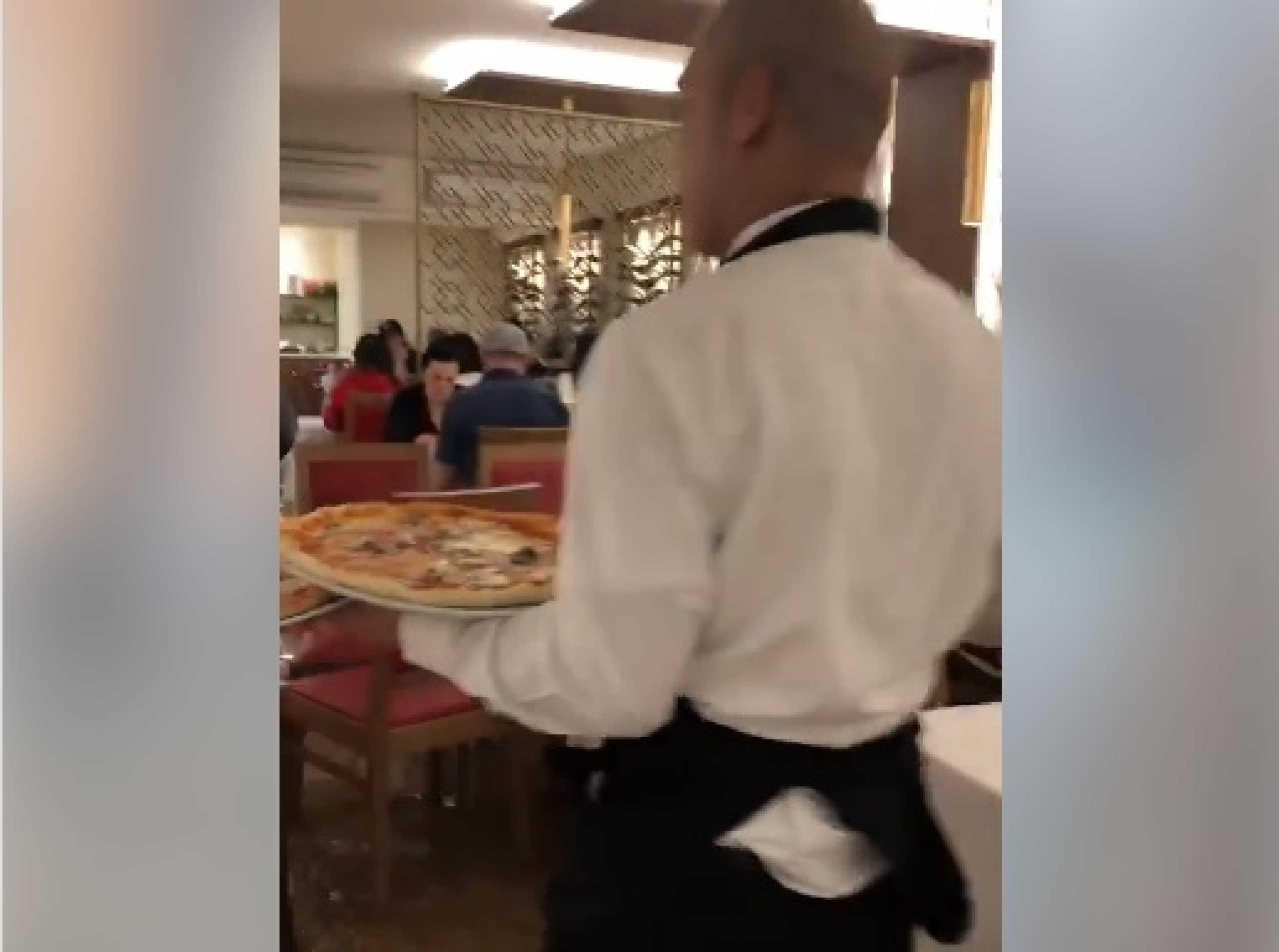 Mesmo com água pelos joelhos, nesta pizzaria não se deixa de trabalhar