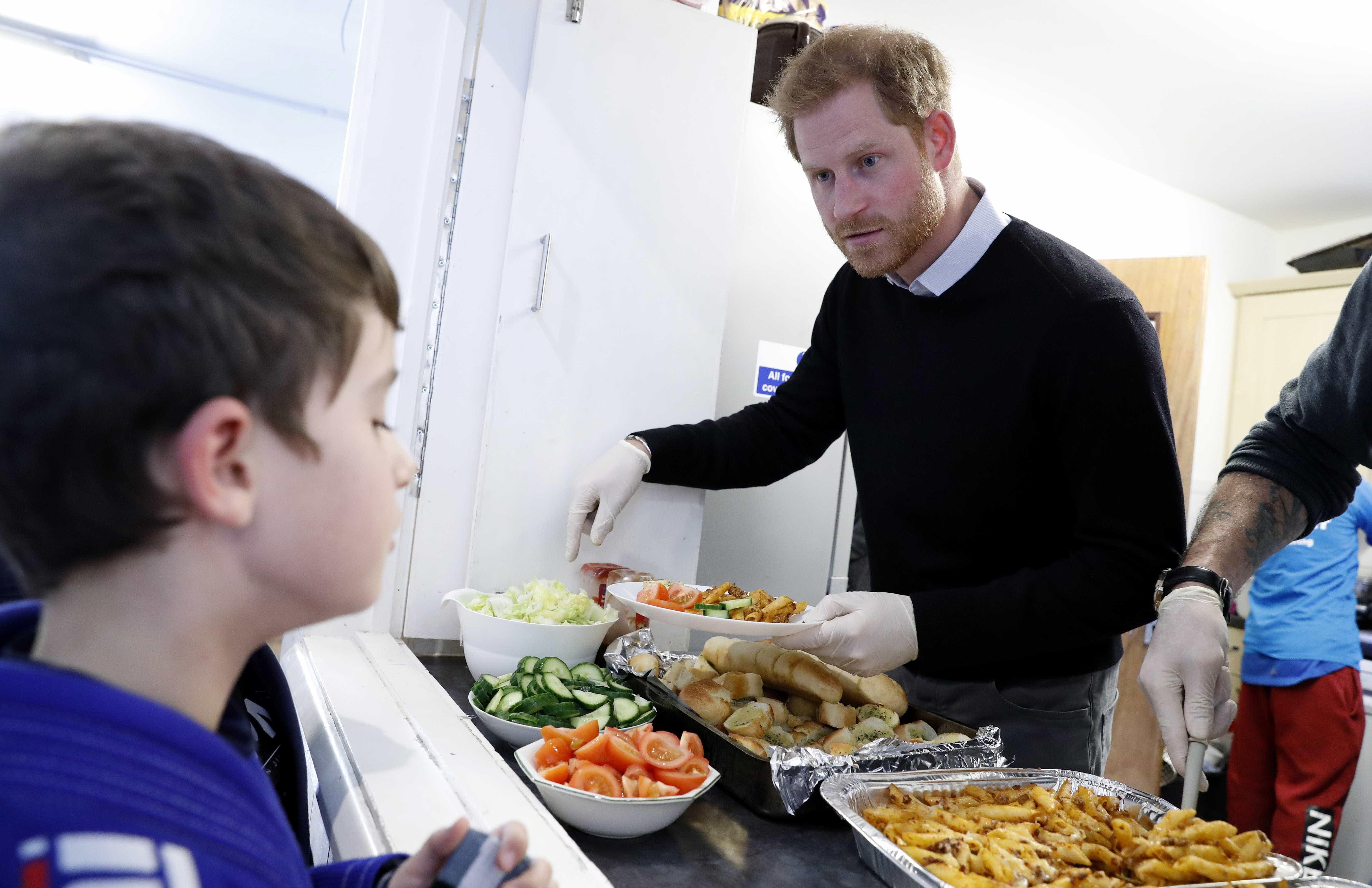 Longe de Meghan Markle, príncipe Harry almoça com jovens